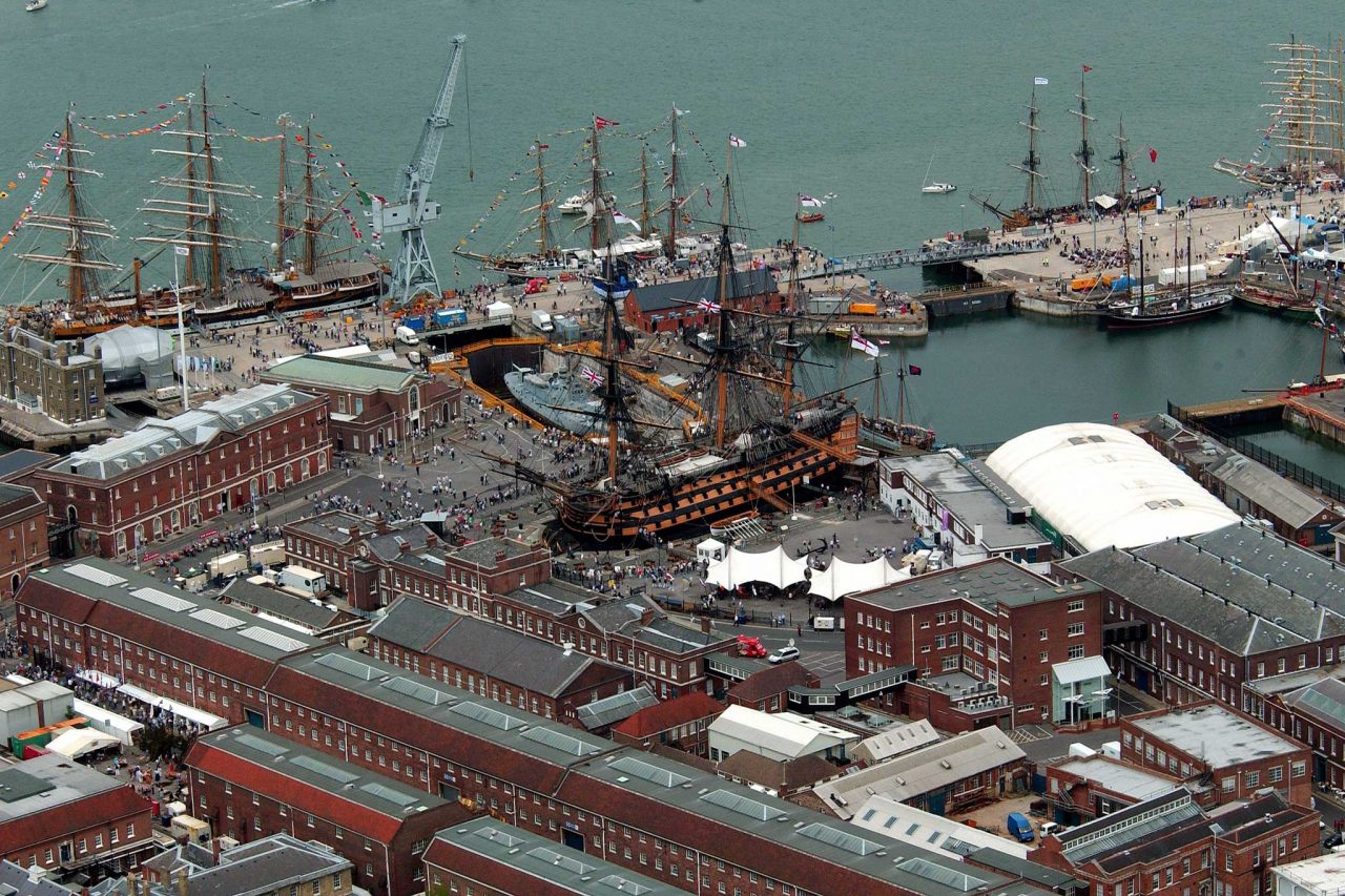 Aerial view of Portsmouth Dockyard, showing HMS Victory and a flotilla of tall ships. Taking part in the International Fleet Review which was part of the Trafalgar 200 celebrations. Mary Rose in dry dock no.3 at right, under white cover. (Photo: UK Government)